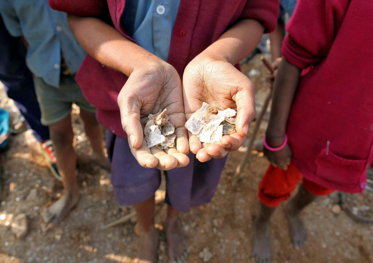 Girl holding mica flakes she collected in Indian mine - Reuters